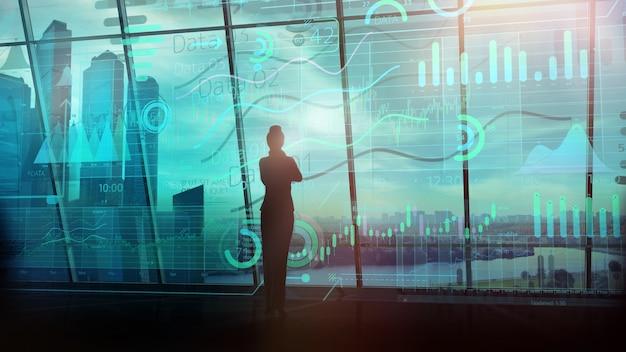 仮想インフォグラフィックデータとパノラマウィンドウの反対側に立っているビジネス女性