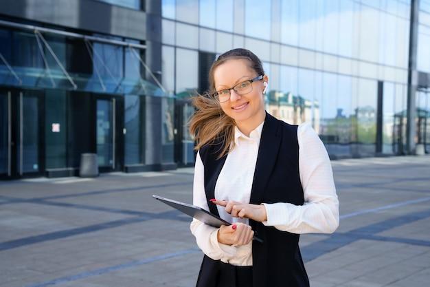 Деловая женщина стоит с ноутбуком в костюме и очках возле офисного здания днем.