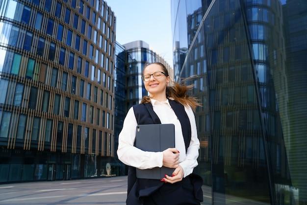 ビジネスウーマンは、日中、オフィスビルの外でスーツと眼鏡をかけたラップトップを持って立っています。