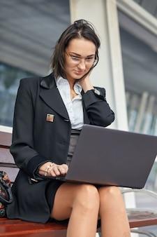 緑豊かな現代の街の通りに座っている間ラップトップコンピューターを使用してビジネス女性