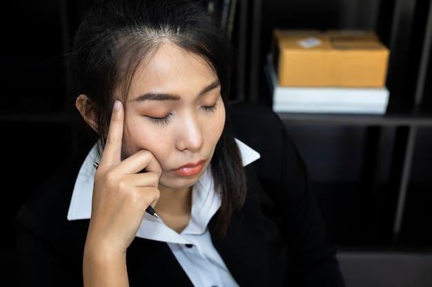 А деловые женщины испытывают стресс в работе. при неисправности, сняв руки, обхватив голову.