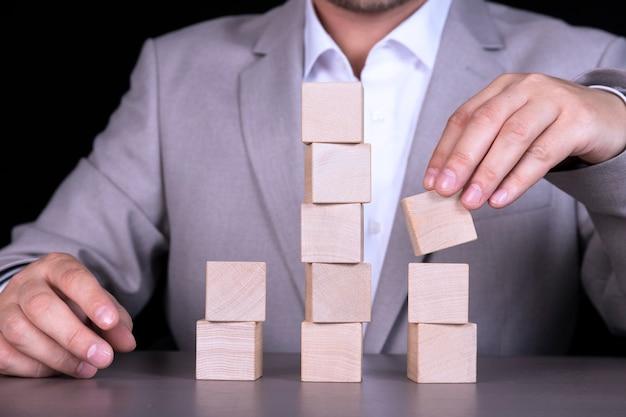 ビジネスマンは、単語やフレーズを書くために10個の木製の立方体のピラミッドを構築します。コピースペース
