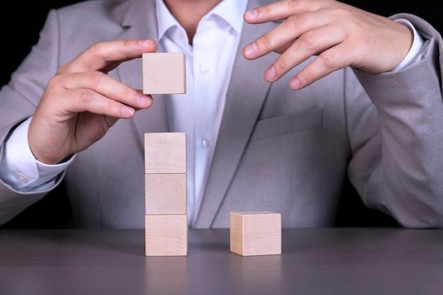 Бизнесмен строит пирамиду из деревянных кубиков, чтобы написать пятибуквенное слово. копировать пространство