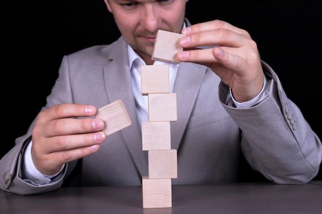 ビジネスマンは、7文字の単語を書くために木製の立方体のピラミッドを構築します。コピースペース