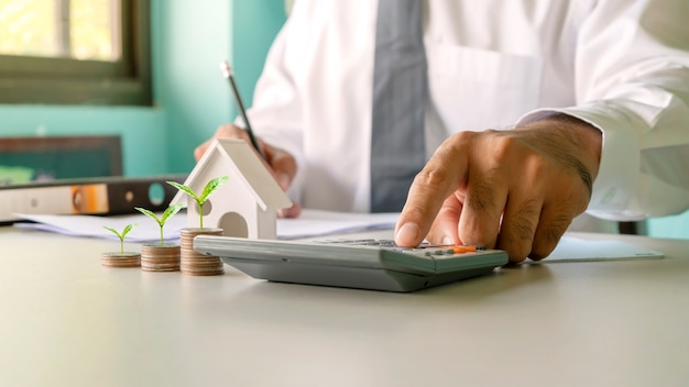 Бизнесмен подсчитывает расходы и анализирует данные об инвестициях в недвижимость