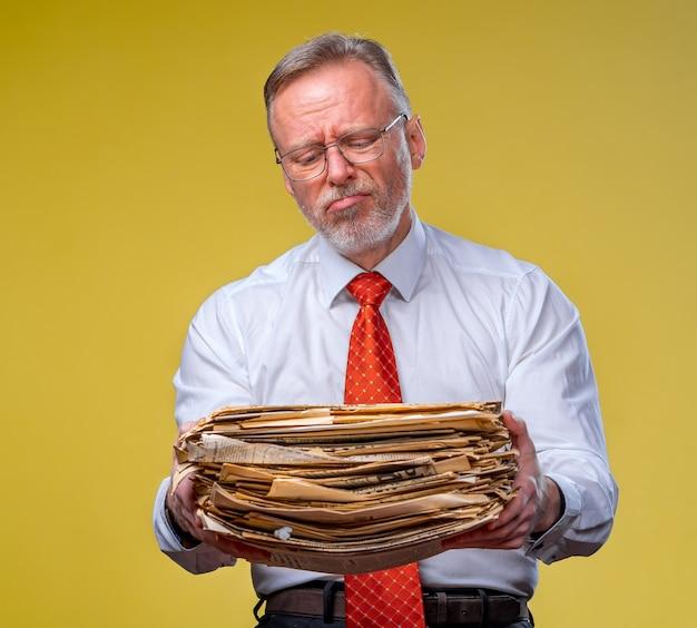 Бизнесмен, несущий кучу документов, на желтом фоне.