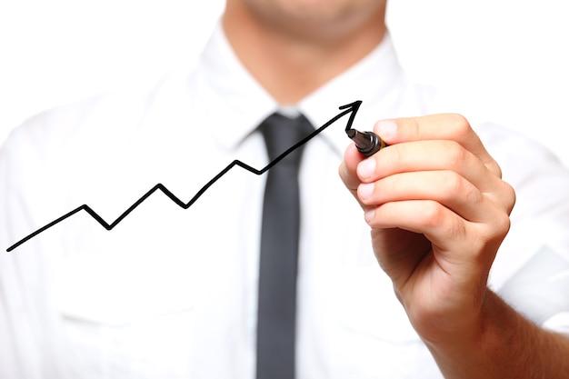 Бизнесмен рисует стрелку, идущую вверх