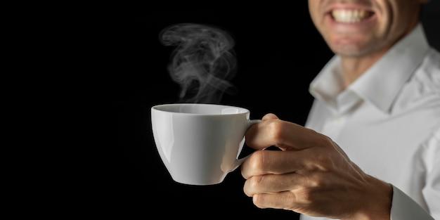 사업가는 휴식 시간에 커피를 마신다. 컵과 검정색 배경에 광고 공간