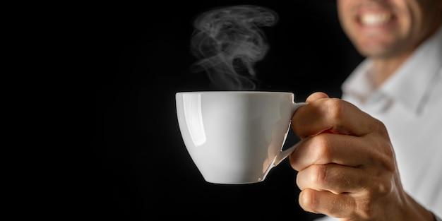 ビジネスマンは休憩中にコーヒーを飲みます。カップと黒の背景に広告スペース