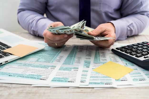 한 사업가가 개인 1040 세금 양식을 작성하고 달러를 계산합니다. 사무실에서 계산기와 종이에 쓰는 남자 손. 회계 개념