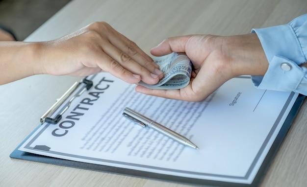 ビジネスマンがビジネス契約に署名するために役人に賄賂を手渡した