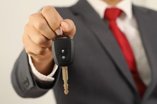 ビジネスマンが修理のために車のキーを従業員に手渡しました。