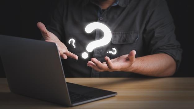 ビジネスマンは、自分のラップトップの前で次に何をすべきか疑問に思う多くの質問をします。