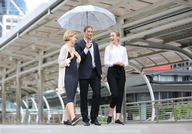 Бизнесмен, держащий зонтик для двух деловых женщин и обсуждение во время прогулки по улице на обед.