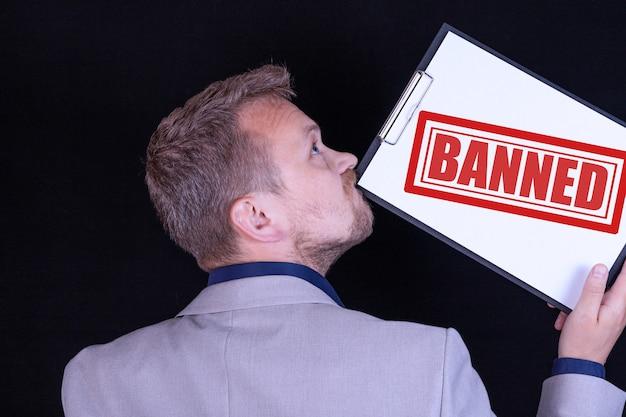ビジネスマンは、「禁止」というテキストが書かれた白紙を持っています。