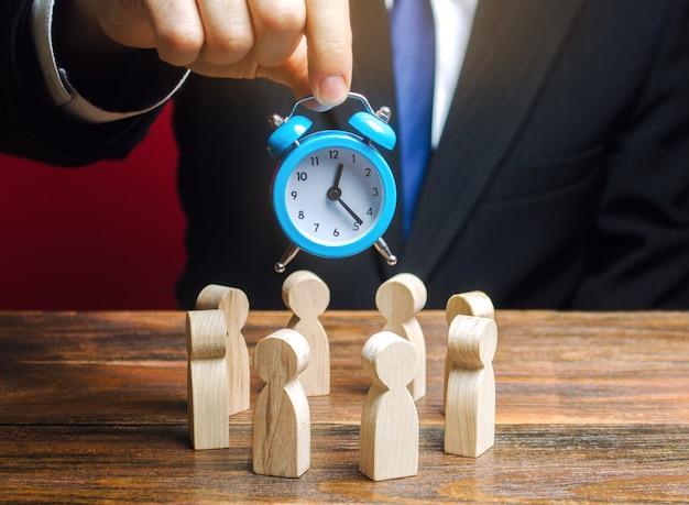 ビジネスマンは、労働者のチームの上に青い時計を保持しています。時間管理のコンセプト。