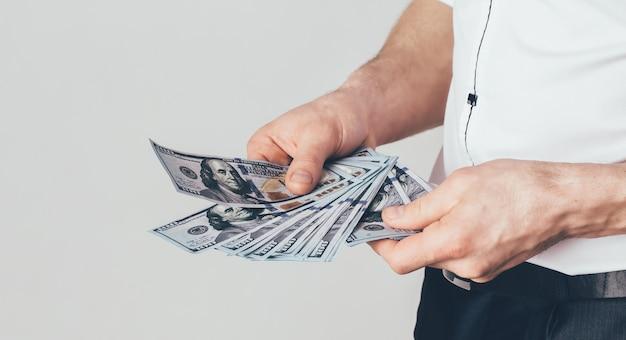 Бизнесмен держит в руках доллары.