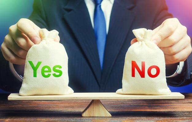 ビジネスマンは、はかりに「はい」と「いいえ」のバッグを持っています。問題の評価と正しい解決策の選択