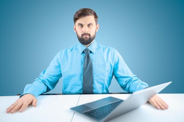 파란색 셔츠와 넥타이를 입은 사업가가 노트북 앞에서 손을 접었습니다.