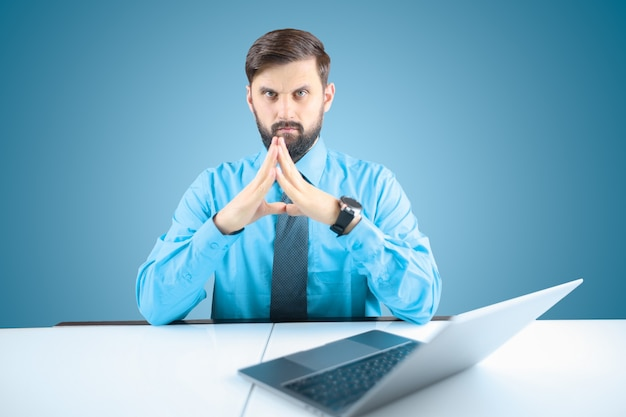 파란색 셔츠와 넥타이를 입은 사업가는 그의 얼굴에 그의 앞에 접힌 손을 가지고 있으며, 단단한 남자는 컴퓨터에 앉아 있습니다
