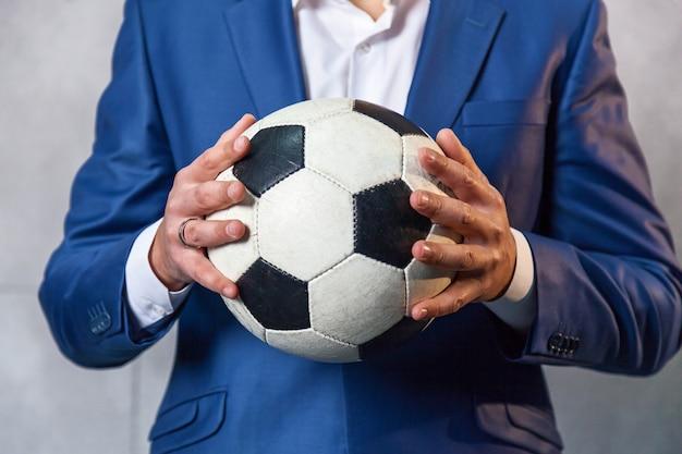 青いスーツを着たビジネスマンが壁の近くに立って、サッカーを手に持っています。