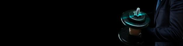 Бизнесмен в темном костюме держит в руке большую тяжелую гантель на темном фоне с местом для текста.