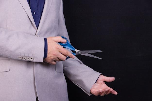 スーツを着たビジネスマンがはさみを手に持っています。ビジネスコンセプト。
