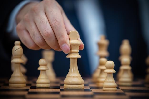 양복을 입은 사업가가 체스 왕을 잡고 있습니다.