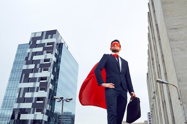 슈퍼 히어로 의상을 입은 사업가가 비즈니스 빌딩에 대항합니다.