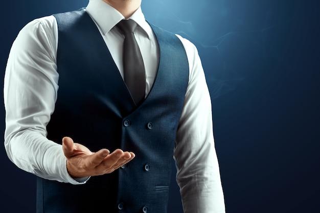 白いシャツのベストとネクタイを着たビジネスマンが手のひらを上に向けて手を差し伸べる