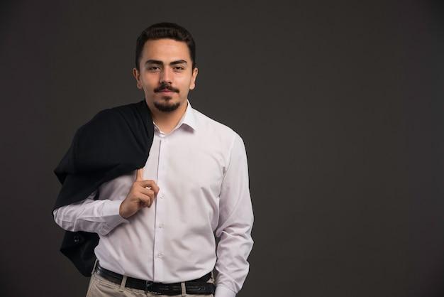 Бизнесмен в дресс-коде, держа на плече черный пиджак.