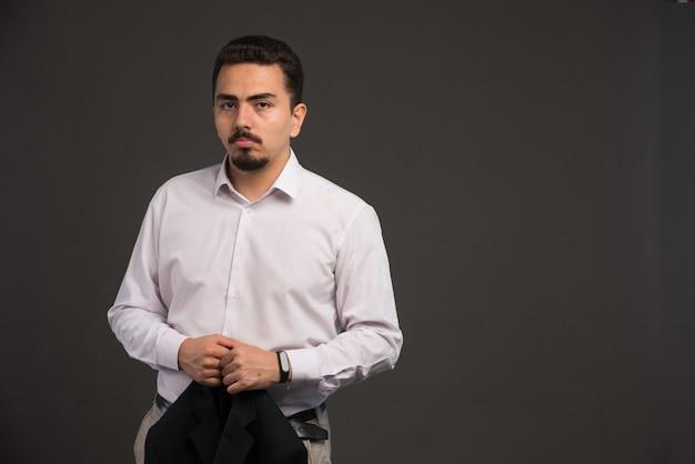 Бизнесмен в дресс-коде с черной курткой.