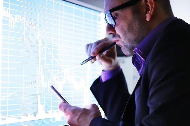 ビジネスマンがモニターでグラフを見ています。取引所ブローカーは株式市場の動向を評価します。経済のダイナミクスの曲線の前に眼鏡をかけた男。