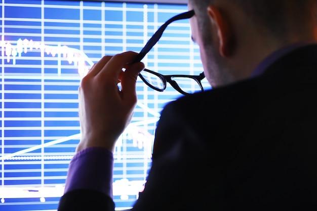 ビジネスマンがモニターでグラフを見ています。取引所ブローカーは株式市場の動向を評価します。経済のダイナミクスの曲線の前に眼鏡をかけた男。 Premium写真