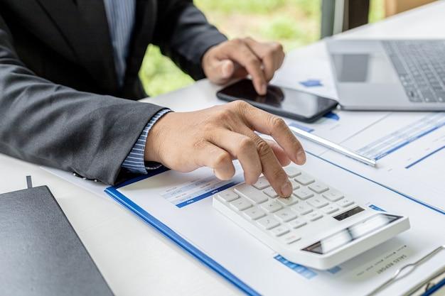 Бизнесмен нажимает на калькулятор, чтобы проверить цифры в документах, он владеет компанией, он проверяет финансовые документы компании в своем офисе, финансовую отчетность. концепция финансового управления.