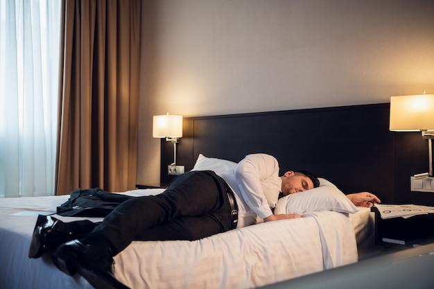 호텔 방에 침대에 누워 사업가