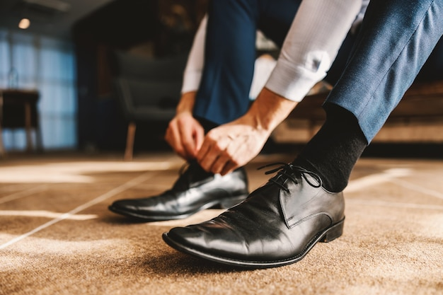 사업가 또는 신랑은 현대적인 실내 공간에서 고전적인 우아한 신발로 차려 입습니다. 손과 신발 클로즈업. 결혼식 날 아름다운 우아한 신발을 레이싱 남성 손의 근접 촬영보기