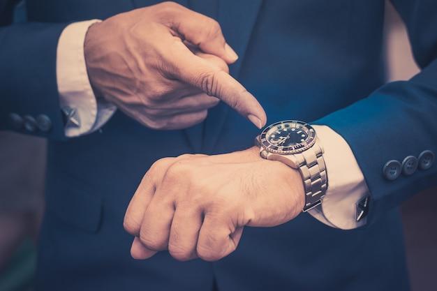 Бизнесмен указывает на наручные часы