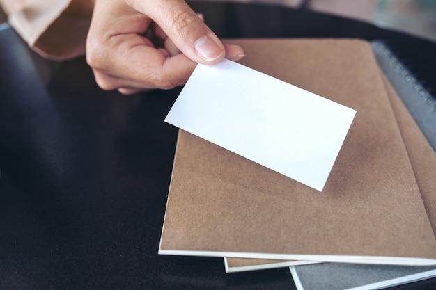 テーブルの上のノートと空のビジネスカードを持っていると与えるビジネスマンの手