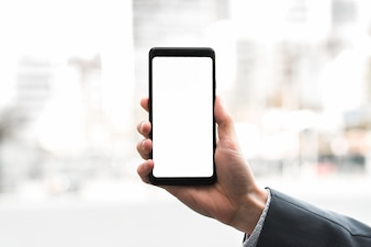 A businessman's hand showing mobile phone against blurred background