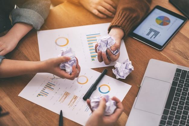 ビジネスマンは、会議でテーブルにラップトップ、タブレット、紙の仕事で手で紙を台無しにした
