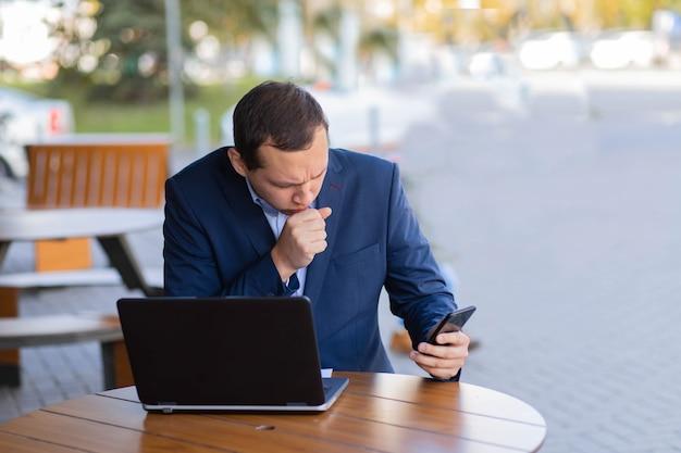 한 사업가가 길가의 카페 테이블에 앉아 손에 기침을하며 금융가에서 휴식 시간에 휴대 전화로 화상 통화를합니다. 일하는 동안의 질병.
