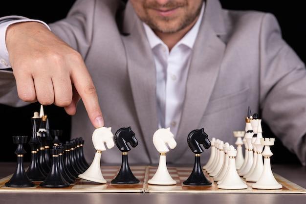 馬の像が描かれているチェス盤の前にビジネスマンが座っている