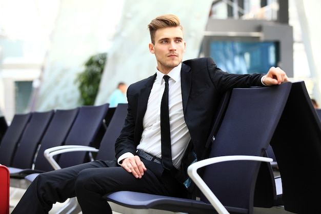 空港に座って、フライトを待っているビジネスマン