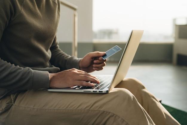 ノートパソコンを膝と手に持って座っているビジネスマンがカードを取ります
