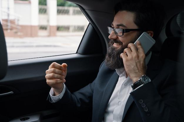 スマートフォンを使用して後部座席で車で旅行中のビジネスマン