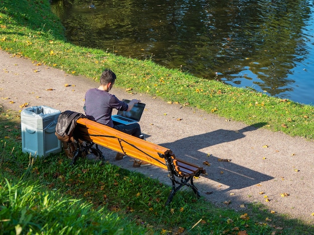 ノートパソコンを持っているビジネスマンは、秋の公園のベンチに座って働いています。