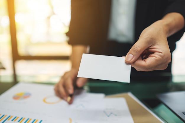 Коммерсантка держа и давая пустую визитную карточку с портативным компьютером и обработку документов на столе в офисе