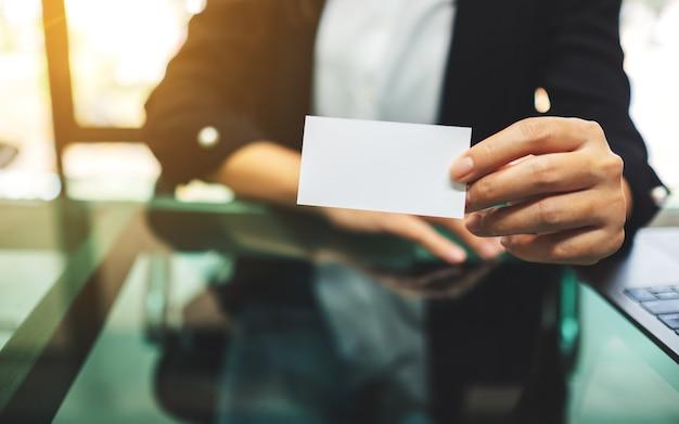 Коммерсантка держа и показывая пустые визитные карточки в офисе