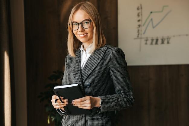 実業家は、会社の新しいプロジェクトを計画している間、手にノートを持ち、オフィスで微笑んでいます。